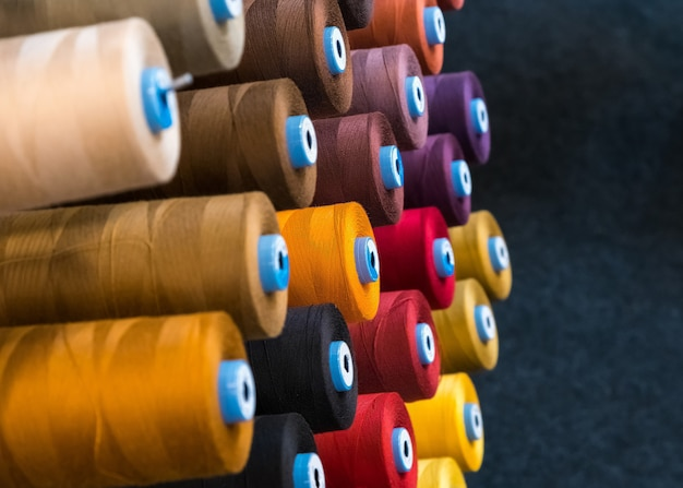 Embroidery thread spool using in garment industry, row of multicolored yarn rolls.