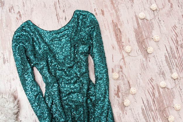 木製の背景にスパンコールと花輪のエメラルドドレス。ファッショナブルなコンセプト。