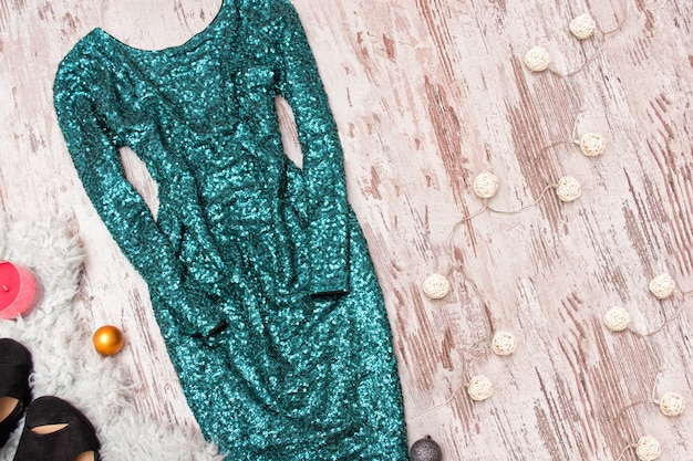 Emerald dress in sequins and garland on a wooden background.