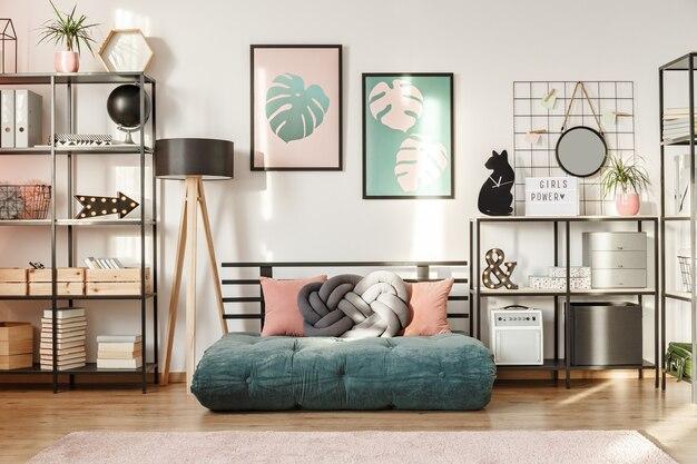 Изумрудный футон с подушками в интерьере современной гостиной с металлическими полками и ботаническими постерами