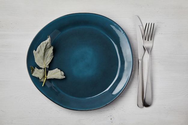 Изумрудная керамическая тарелка ручной работы со столовыми приборами на белом деревянном столе. меню верхнего вида