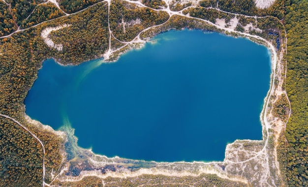 Emerald lake in a flooded quarry in the forest, aerial view