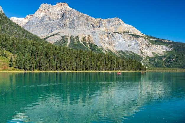 Изумрудное озеро летом с лесом и горами позади