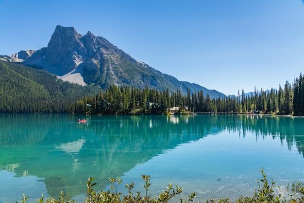 잎이 무성한 숲과 산이 가득한 여름의 에메랄드 호수