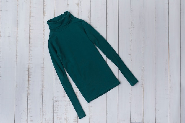 Emerald turtleneck on a wooden background. fashionable concept