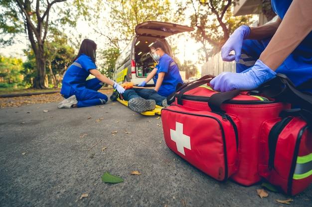 Пациент в аварийной ситуации. пострадал на голове, лежа на носилках. обучение оказанию первой помощи и перемещение пациента в аварийной ситуации. фельдшер переводит пациента в машину скорой помощи. выберите сосредоточьтесь на сумке первой помощи.