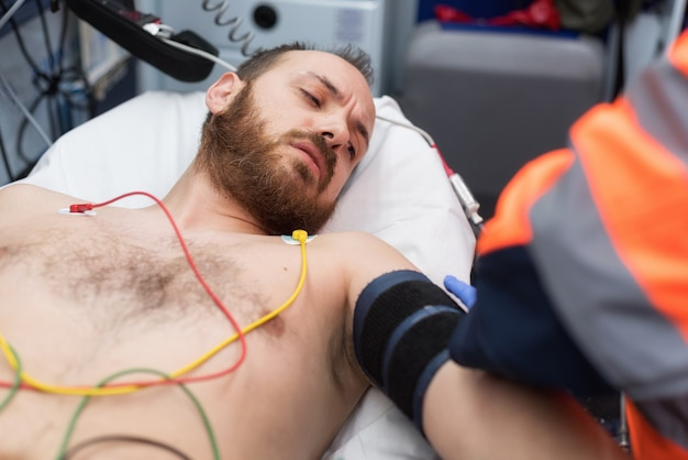 Emergency doctor checking blood pressure of a patient in the ambulance