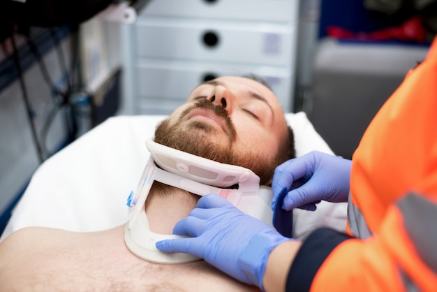Emergency doctor putting a cervical collar to a patient in the ambulance
