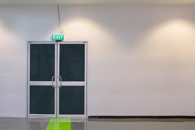 비상구 흰 벽에 알루미늄 흰색 프레임 문 및 크롬 도어 핸들