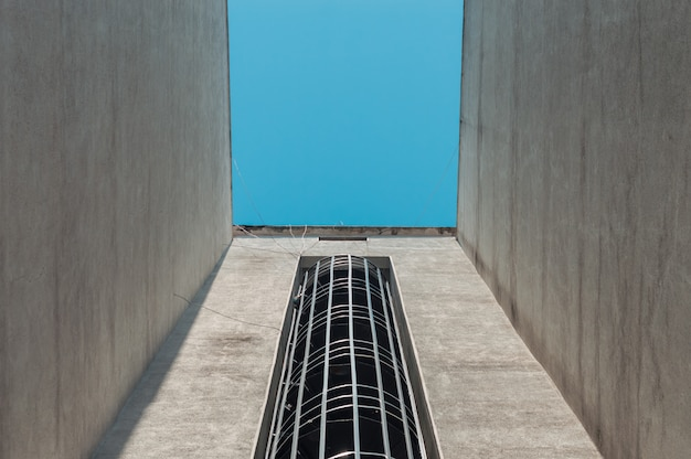 Emergency fire escape staircases on a building exterior with blue sky above