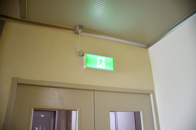 Знак аварийного пожарного выхода указывает путь к спасению.