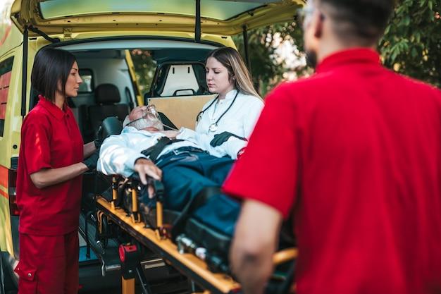 Скорая медицинская помощь на работе. фельдшер тащит носилки с пожилым мужчиной с тяжелым сердечным приступом в машину скорой помощи. помощь в дороге. концепция помощи водителям.