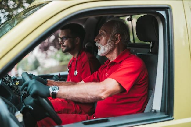 Работники службы неотложной медицинской помощи за рулем машины скорой помощи.