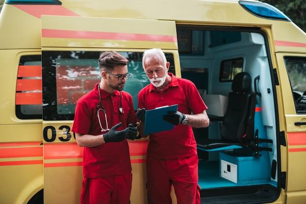 Работники-мужчины службы неотложной медицинской помощи стоя и позируют перед машиной скорой помощи.