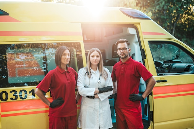 Работники скорой медицинской помощи мужчина и женщина стоя и позирует перед машиной скорой помощи.