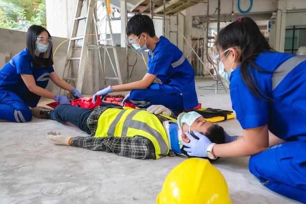 救急医療チームは、建設現場で足の骨折事故を起こした建設作業員を支援しています。安全チームは従業員の事故を支援します。