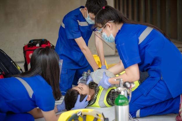 救急医療チームは、自動体外式除細動器(aed)を使用し、酸素を供給することで、意識不明の患者を支援しています。建設現場での意識不明の労働者の救助中