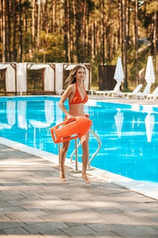 Emergency. a pretty female lifeguard running near the pool