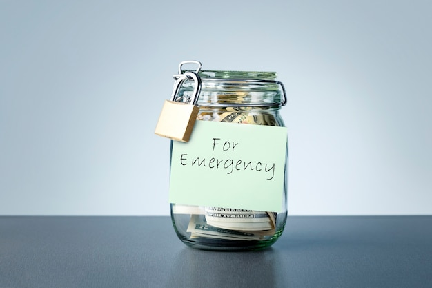 For emergency savings written on the jar with dollars banknotes money. concept of money saving for rainy day.