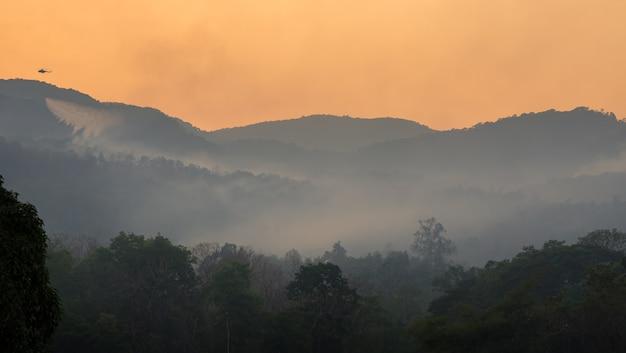 Вертолет экстренных служб сбрасывает воду для тушения лесных пожаров, которые сожгли лес в горах.