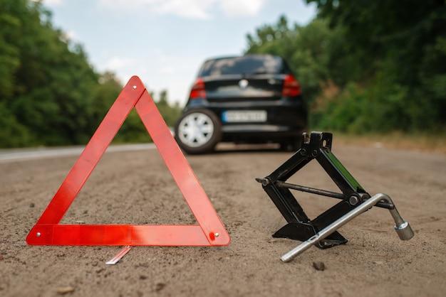 Знак аварийной остановки и домкрат, поломка автомобиля.