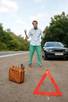 Знак аварийной остановки и канистра с бензином