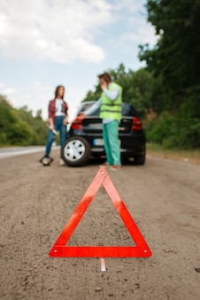 Emergency stop sign, car breakdown, couple calling for tow truck.