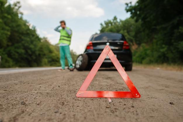 非常停止標識、車の故障、レッカー車を呼ぶ男。自動車の故障やパンクした車両の修理、高速道路でのパンクした自動車タイヤのトラブル