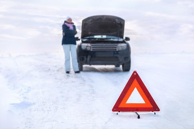 비상 정지 신호. 난파 된 차 근처의 여자가 얼어 붙는다. 눈 덮인 겨울 필드 주변.
