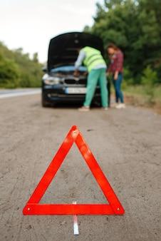 Знак аварийной остановки, молодая пара у открытого капота на дороге, поломка автомобиля. разбитый автомобиль или аварийная авария с автомобилем, неисправность двигателя на шоссе