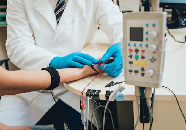 Тестирование нервов пациента с помощью электромиографии. emg