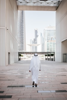 Emirates urban lifestyle in the big city with arab guy investor checking out the city in gulf country.