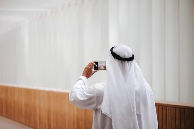 Emirati guy taking selfie in the urban city lifestyle downtown the heart of dubai