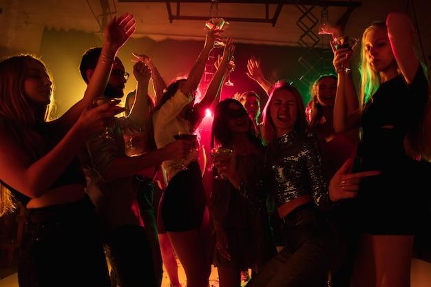 감정. 실루엣의 사람들이 손을 들고 네온 불빛 배경의 댄스플로어에서 춤을 춥니다. 나이트 라이프, 클럽, 음악, 댄스, 모션, 젊음. 밝은 색상과 움직이는 소녀와 소년.