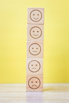Emotion face blocks on yellow background. service rating, ranking, customer review, satisfaction, evaluation and feedback concept