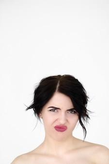 Эмоция лицом отвращения. неохотно недовольна женщина на белой стене.