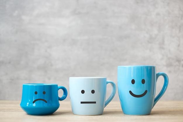 블루 커피 컵의 감정 얼굴입니다. 고객 리뷰를 위해. 서비스 등급, 순위, 만족도, 평가 및 피드백 개념. 세계 미소의 날과 국제 커피의 날