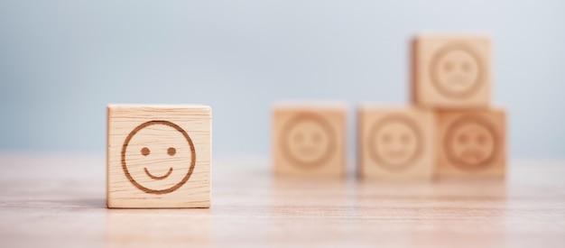 Символ лица эмоции на деревянных блоках. рейтинг услуг, ранжирование, обзор клиентов, удовлетворенность, оценка и концепция обратной связи