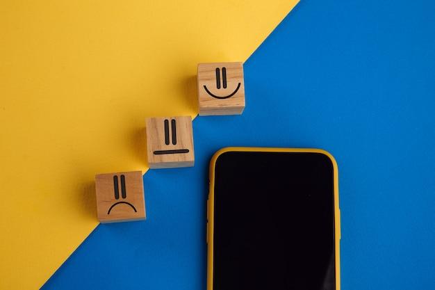 Символ лица эмоции на деревянных кубических блоках и смартфоне. рейтинг обслуживания, рейтинг, обзор клиентов, концепция удовлетворенности и обратной связи.