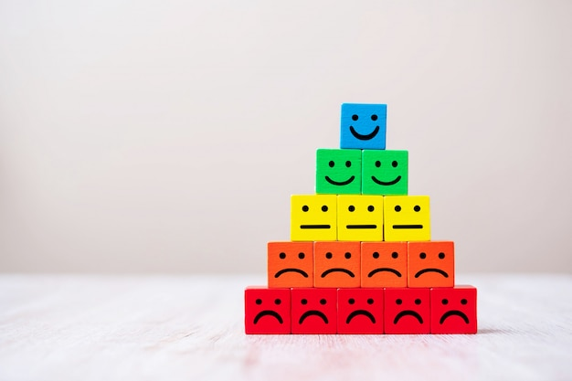 Символ лица эмоции на деревянных кубических блоков. сервис рейтинг, рейтинг, обзор клиентов, удовлетворенность и концепция обратной связи.