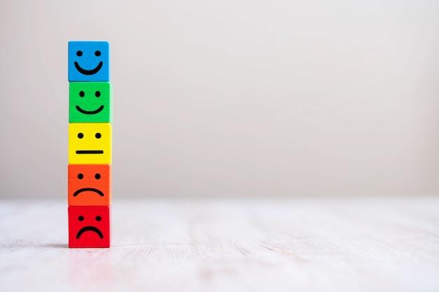 黄色の木製キューブブロックの感情面記号。サービスの評価、ランキング、顧客レビュー、満足度、フィードバックの概念。