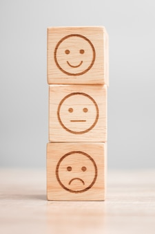Emotion face symbol on wooden blocks. service rating, ranking, customer review, satisfaction, evaluation and feedback concept