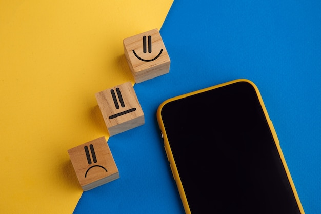 Emotion face symbol on wooden cube blocks and smartphone