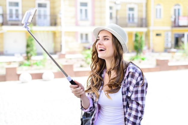 Emotion facial expression people person webcam concept. side profile close up portrait of charming pretty beautiful cute positive funny funky optimistic girl making taking selfie building background