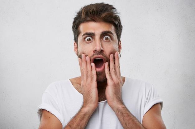 Emozione, persone e concetto di linguaggio del corpo. uomo sorpreso con pettinatura alla moda e setola con occhialino
