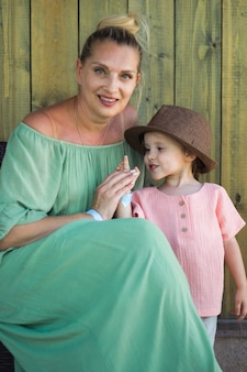 Emotion portrait grandmother and his granddaughter in rural style clothers on wooden background