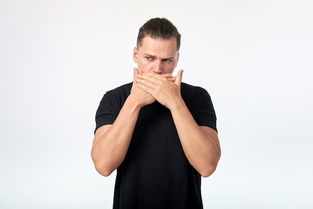 Emotion. portrait of young scared man covering his mouth with hands.