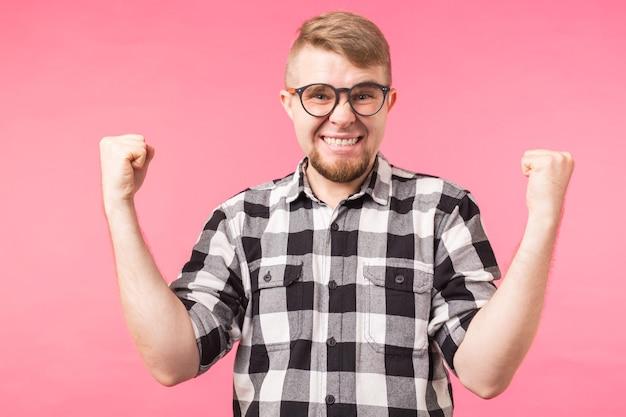 Эмоции, успех, жест и люди концепции - молодой человек в очках празднует победу над розовым фоном.