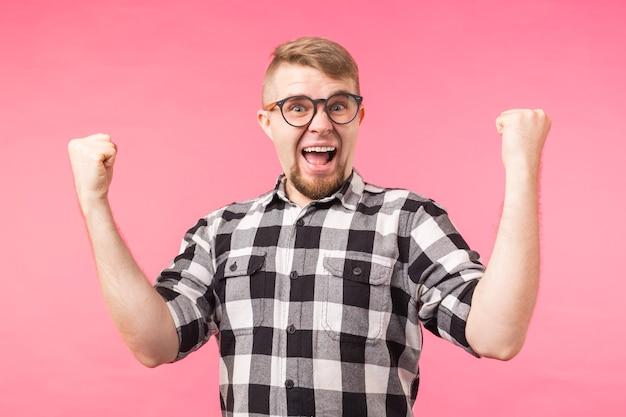 Эмоции, успех, жест и люди концепции - молодой человек в очках празднует победу над розовым