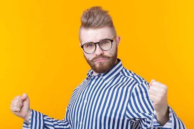 Эмоции, успех, жест и люди концепции - молодой человек в очках празднует победу над желтым